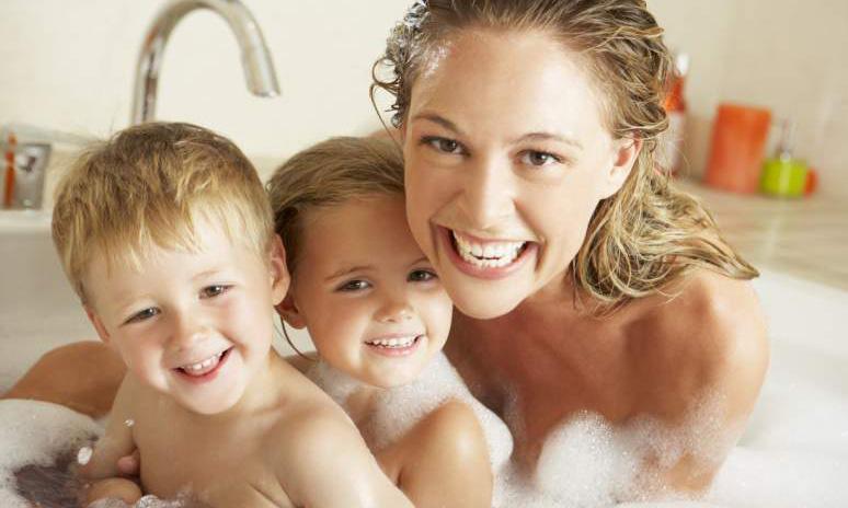 Moeder met twee kinderen in een bad vol schuim